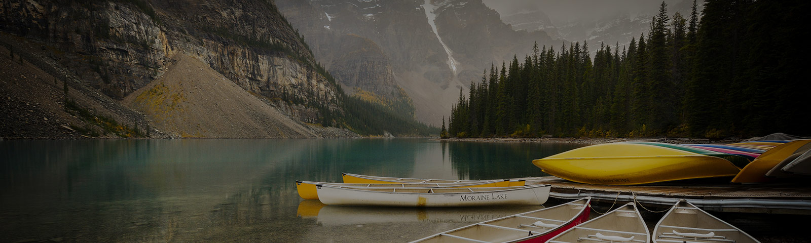 canoes on a lake between mountains