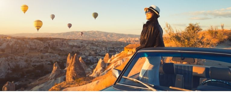 Allianz - woman watching colorful hot air balloons flying over the valley at Cappadocia